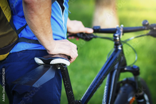 Fototapeta Close-up of cyclist rides bicycle against green park background. Ride bike in the summer. Leisure. Sports and healthy lifestyle concept obraz