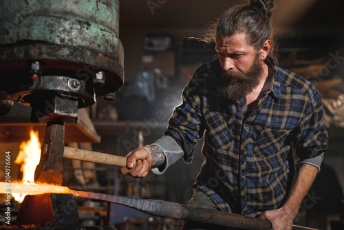 Fotografering Real brutal blacksmith works in a workshop mechanical hammer with a red-hot iron