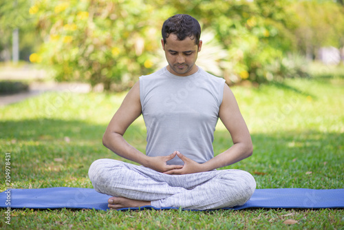 Focused Indian Guy Doing Yoga Asanas In Park Young Man Relaxing Outdoors And Meditating In Lotus Pose With Closed Eyes Meditation And Life Balance Concept Buy This Stock Photo And Explore