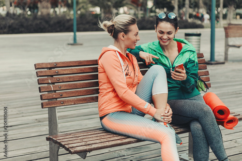 Papiers peints Ecole de Danse Happy two girls are talking and laughing while sitting on bench outdoor. Lady is showing smartphone to her friend. They are wearing sportswear