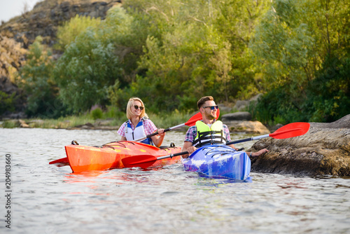 Young Happy Couple Paddling Kayaks on Beautiful River or Lake