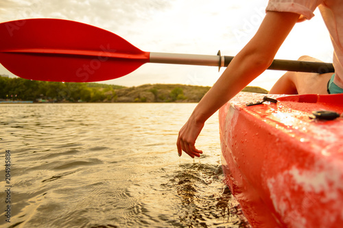 Valokuva  Young Woman Playing with Water while Sitting in Kayak on Beautiful River or Lake at Sunset