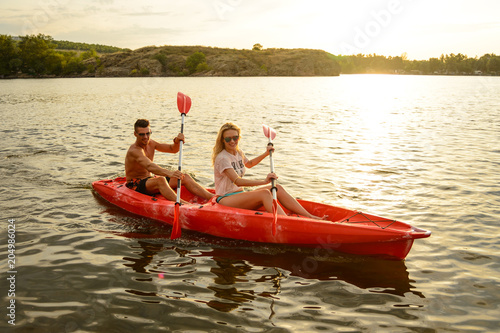 Fototapeta Young Couple Paddling Kayak on Beautiful River or Lake in the Evening at Sunset