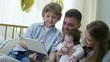 PAN of happy young parents with elementary age boy and cute baby girl talking and watching something on tablet