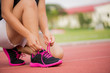 Running shoes - closeup of Young woman tying shoe laces. Female sport fitness runner getting ready for jogging on Running Track. Healthcare and sport concept.