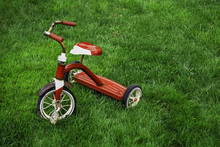 Old Red Tricycle On Green Grass