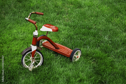 Recess Fitting Bicycle old red tricycle on green grass