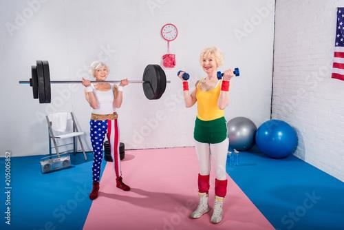 Fotografía smiling senior sportswomen exercising with dumbbells and barbell in gym