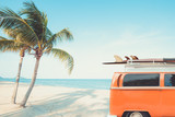 zabytkowy samochód zaparkowany na tropikalnej plaży (nad morzem) z deską surfingową na dachu - wycieczka wypoczynkowa w lecie. efekt koloru retro - 205009208