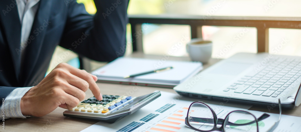 Fototapeta Businessman using calculator for analysis maketing plan, Accountant calculate financial report, computer with graph chart.  Business, Finance and Accounting concepts