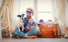 Young Girl With Little Baby And A Dog Sitting Next To Suitcase Before Travel Near A Window At Home