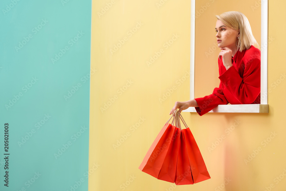 Fototapeta pensive fashionable woman in red clothing with red shopping bags looking out decorative window