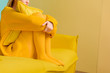 Leinwandbild Motiv partial view of woman in yellow sweater and tights sitting on yellow sofa