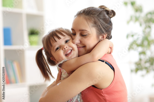 Obraz love and family concept - happy mother and child daughter hugging at home - fototapety do salonu