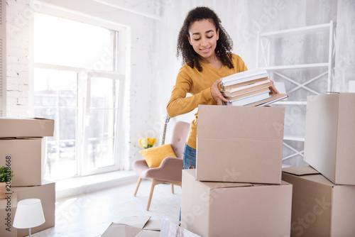 Obraz Favorite books. Pleasant curly-haired girl packing a pile of books into a big box before moving out of the room in the dormitory - fototapety do salonu