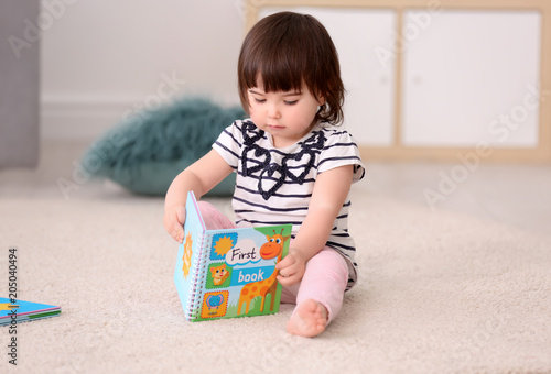 Stampa su Tela Cute baby girl with book sitting on floor at home