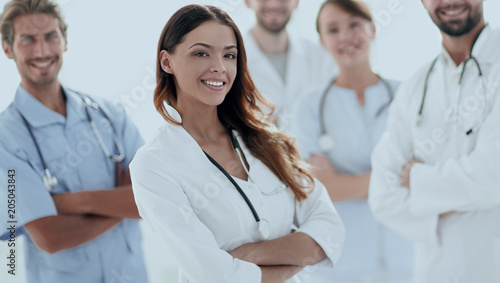 Fotobehang Stof Attractive female doctor with medical stethoscope in front of medical group