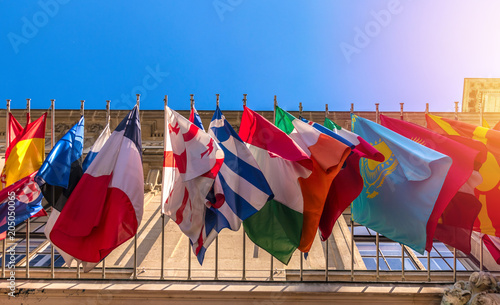 Fototapeta  Different flags of many countries on building facade, sky background