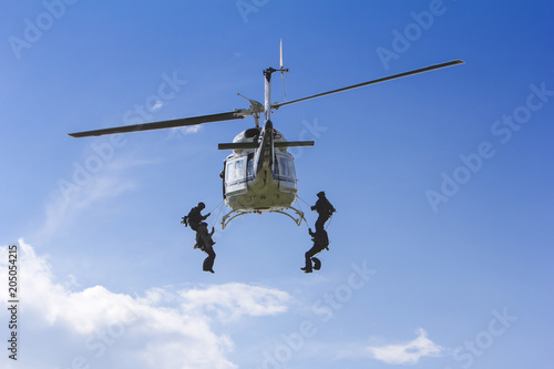 Keuken foto achterwand Helicopter Special forces in helicopter with blue sky on background