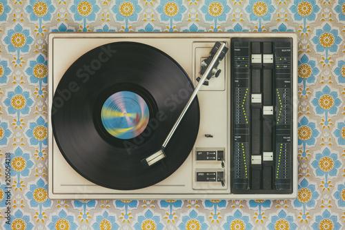 Fotografía Record player on top of flower wallpaper