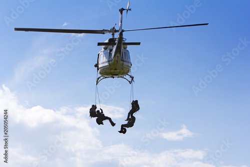 Special forces in helicopter with blue sky on background