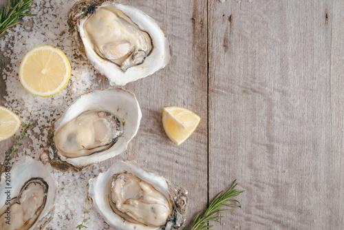 Dozen fresh oysters on a sea salt and lemon. Top view © makistock