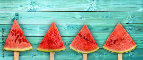 Four watermelon slice popsicles on panoramic blue wood background, fresh summer fruit concept