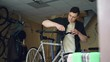 Skilled mechanic is fixing handle-bar of modern bicycle using professional tools in workshop with spare parts and equipment. Bike maintenance and people concept.