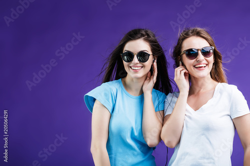 Papiers peints Magasin de musique Cute smiling girls dressed in t-shirts and sunglasses listen to the music via earphones before blue background
