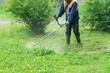 Leinwanddruck Bild - The gardener cutting grass by lawn mower