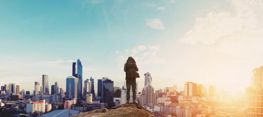 Fototapeta na wymiar a man with backpack standing on the mountain enjoying beautiful sunrise in the city
