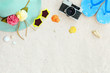 Beach background. Top view of beach sand with straw hat, sunglasses, shells, camera, slippers and coral. Summer background concept.