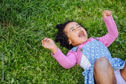 Portrait of capricious dark skinned hispanic or mexican toddler girl crying on green grass Tapéta, Fotótapéta