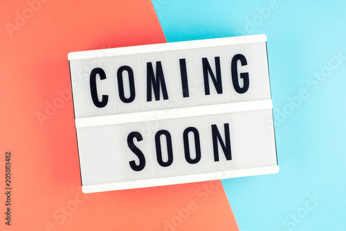 Coming soon - text on a display lightbox on blue and red bright background.