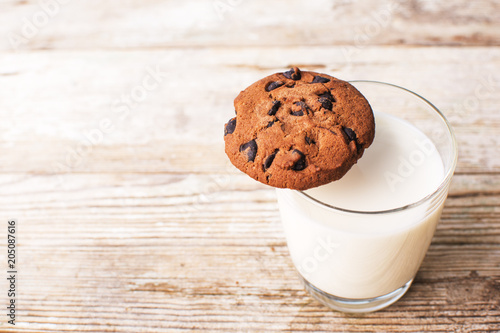 Tuinposter Koekjes chocolate chip cookies and a glass of milk on an old board, top view