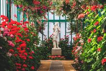 Beautiful Female Statue In Colorful Blooming Orangery. Royal Greenhouses Of Laeken In Belgium