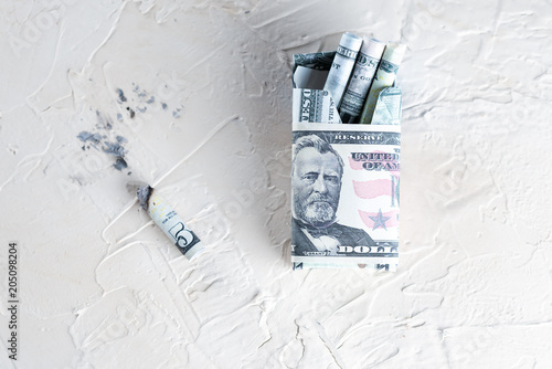 Fotografie, Obraz  Pack of cigarettes with dollar bills and Cigarette butt on white background