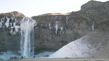 A Cluster Of Tourists Near The Winter Waterfall.