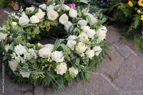 Leinwand Poster Trauerkranz mit Blumen auf dem Friedhof