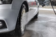 Detail on silver car front wheel being washed with jet water spray in carwash.