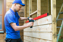 Shed Construction - Worker Installing Wooden Facade Planks