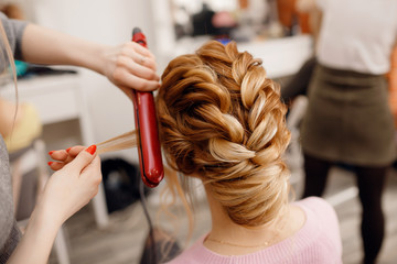 Woman hairdresser making hairstyle to blonde girl in beauty salon.