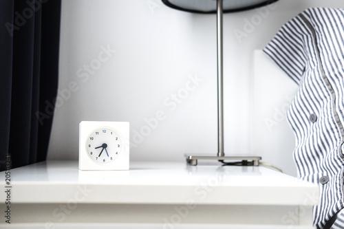 Photo Morning alarm clock in white bedroom interior