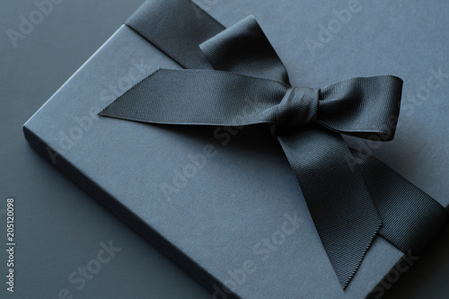 Photo  Black gift box on a dark contrasted background, decorated with a textured bow and feathers, creating a romantic atmosphere