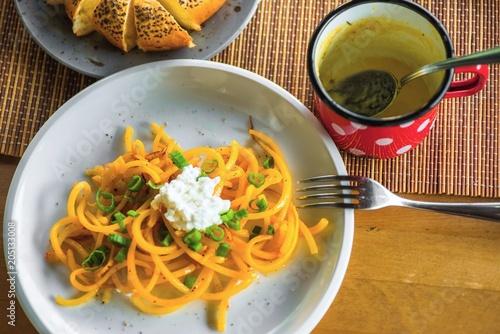 Staande foto Klaar gerecht Table with pumpkin noodle,rest of soup and bread.