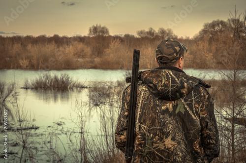 Poster Chasse Hunter man shotgun camouflage exploring flood river hunting season rear view sunset