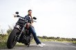Stylish man in denim leaning on motorbike and looking away on road with summer nature on background.