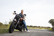 Handsome trendy man leaning on motorcycle standing on remote rural road and smiling in sunlight.