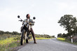 Casual man sitting on motorbike and looking around in enjoyment of nature and traveling looking happy.