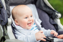 Portrait Of Funny Baby Boy Laughing Outdoors. Cute Adorable Child Having Fun Sitting In Stroller During Walk